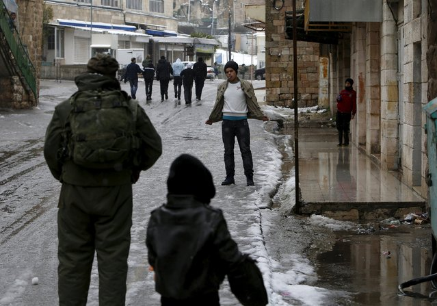 An Israeli soldier inspects a Palestinian during a snow storm in West Bank old city of Hebron, January 26, 2016. (Photo by Mussa Qawasma/Reuters)