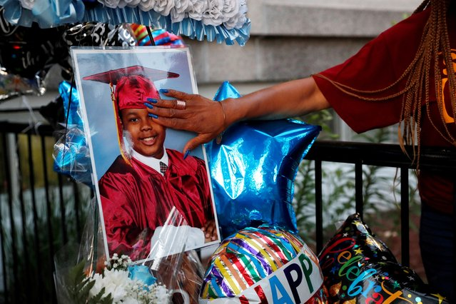 A person touches the photograph of 10-year-old Justin Wallace, who was shot and killed when a shooter fired rounds at a home in the Far Rockaway section of Queens Saturday evening according to the New York Police Department, during a community vigil outside the Challenge Preparatory Charter School he attended in New York City, U.S., June 10, 2021. (Photo by Shannon Stapleton/Reuters)