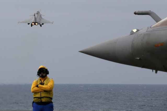 A yellow dog deck officer stands on the flight deck as a Rafale fighter jet takes off from France's Charles de Gaulle aircraft carrier in the Gulf, January 27, 2016. (Photo by Philippe Wojazer/Reuters)