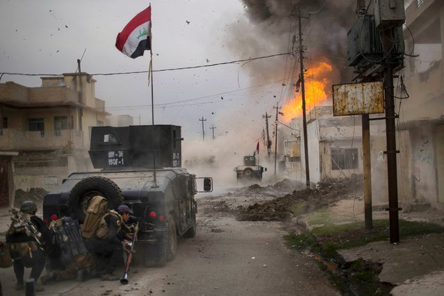 A car bomb explodes next to an Iraqi special forces armored vehicle as they advance toward territory held by the Islamic State group in Mosul, Iraq, on November 16, 2016. (Photo by Felipe Dana/AP Photo)