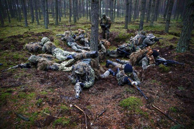 Participiants secure a position during a territorial defence training organised by paramilitary group SJS Strzelec (Shooters Association) in the forest near Minsk Mazowiecki, eastern Poland March 14, 2014. (Photo by Kacper Pempel/Reuters)
