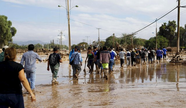 Locals cross a flooded river at Copiapo city, March 26, 2015. (Photo by Ivan Alvarado/Reuters)