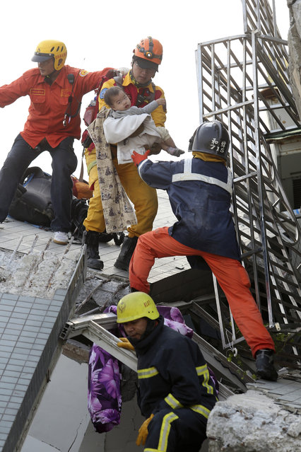 A child is rescued from a toppled building after a 6.4-magnitude earthquake in Tainan, Taiwan, Saturday, February 6, 2016. The earthquake struck southern Taiwan early Saturday, toppling at least one high-rise residential building and trapping people inside. (Photo by AP Photo)