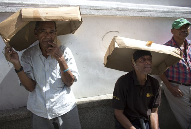 In this Friday, August 3, 2018 photo, men utilize cardboard boxes to shade themselves from the sun's rays as they wait in line to take part in a vehicle census announced by Venezuela President Nicolas Maduro, in the first step to regulate the sale of gasoline, in Caracas, Venezuela. (Photo by Ariana Cubillos/AP Photo)