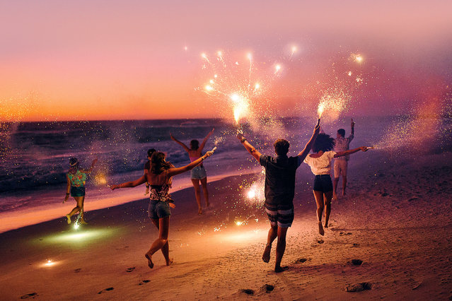 Friends running with fireworks on a beach after sunset. (Photo by Wundervisuals/Getty Images)