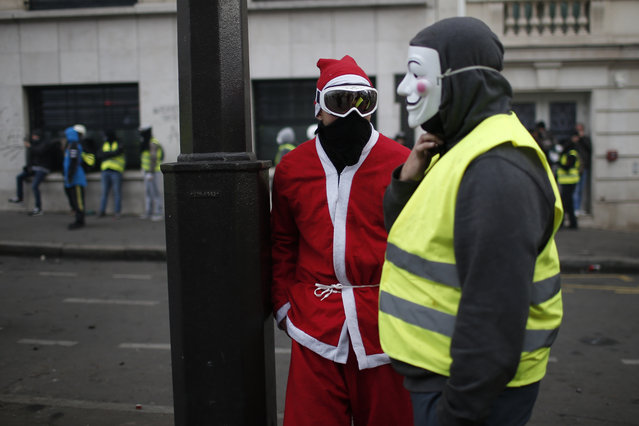 Demonstrators, one dressed like a Santa Claus, talk during clashes Saturday, December 8, 2018 in Paris. (Photo by Rafael Yaghobzadeh/AP Photo)