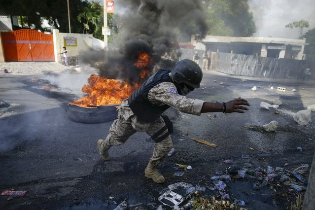 Police clear barricades of burning tires set by protesters upset with growing violence in the Lalue neighborhood of Port-au-Prince, Haiti, Wednesday, July 14, 2021, a week after Haitian President Jovenel Moise was assassinated in his home. (Photo by Joseph Odelyn/AP Photo)