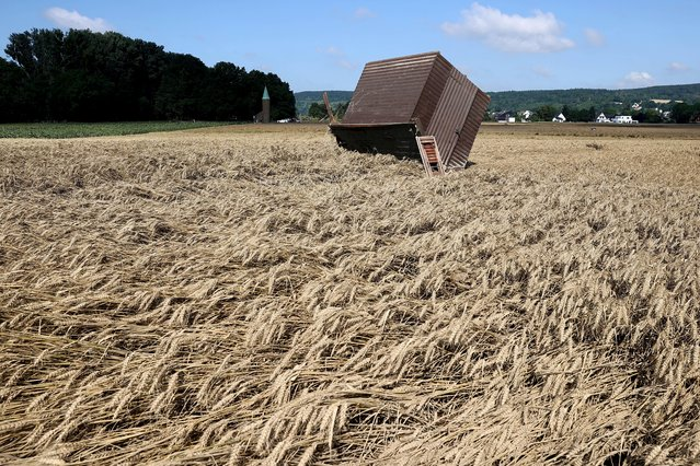 A damaged wooden garden house is seen amid a field of wheat following floods caused by heavy rainfalls, in Bad Bodendorf, Germany, July 18, 2021. (Photo by Wolfgang Rattay/Reuters)