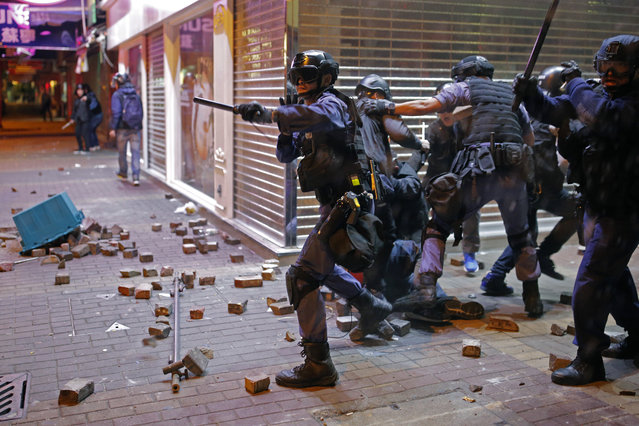 Riot police officers react as rioters set fires and throw bricks at them in Mong Kok district of Hong Kong, Tuesday, February 9, 2016. (Photo by Vincent Yu/AP Photo)