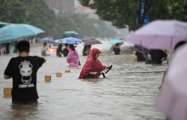 Residents wade through floodwaters on a flooded road amid heavy rainfall in Zhengzhou, Henan province, July 20, 2021. (Photo by China Daily via Reuters)