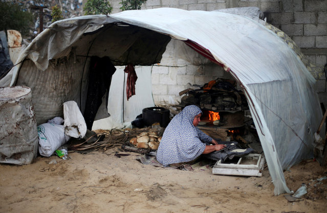 A Palestinian woman bakes bread in a tent outside her dwelling in Khan Younis in the southern Gaza Strip December 19, 2016. (Photo by Ibraheem Abu Mustafa/Reuters)