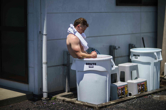 Australia's Henry Hutchison takes an ice bath in a garbage bin following a men's rugby sevens practice at the Tokyo 2020 Olympics, in Tokyo, Friday, July 23, 2021. (Photo by David Goldman/AP Photo)