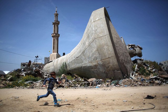 A Palestinian child runs past a water tank that was destroyed in Israeli bombing during the 50-day war between Israel and Hamas militants in the summer of 2014, in the village of Khuzaa, east of Khan Yunis, in the southern Gaza Strip on March 26, 2015. (Photo by Said Khatib/AFP Photo)