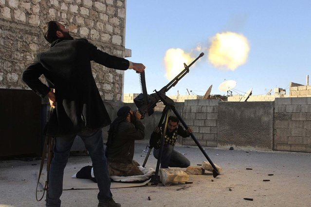 "A ""Free Syrian Army"" fighter holds up an ammunition belt  as his fellow fighter fires on a helicopter belonging to the Syrian regime in Aleppo's Bustan al-Basha district, on December 6, 2013. (Photo by Molhem Barakat/Reuters)"