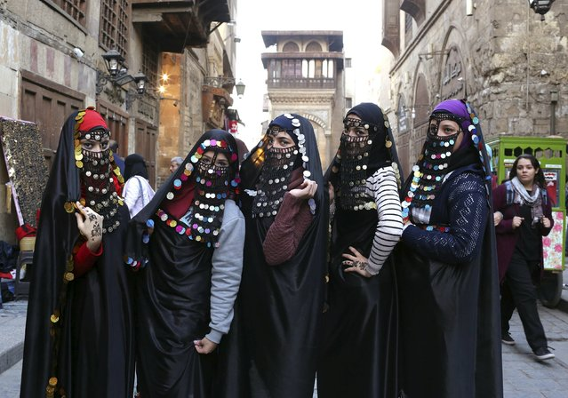 Girls dressed up in traditional Egyptian clothes from the early 20th century pose for a picture before they get their photos taken on the historical Al-Moez street of Islamic Cairo, Egypt, January 17, 2016. (Photo by Asmaa Waguih/Reuters)