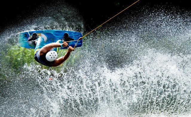 A man jumps with his wakeboard at the water ski facility at the Blauer See in Garbsen on August 5, 2018. (Photo by Peter Steffen/AFP Photo/DPA)