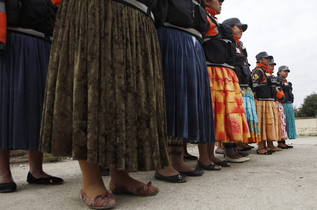 """In this December 13, 2013, so-called """"traffic cholitas"""" stand in formation before heading out to the streets to control and direct traffic in El Alto, Bolivia. (Photo by Juan Karita/AP Photo)"""