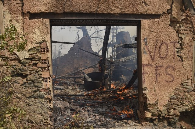 A house burns during a wildfire in Tizi Ouzou, one of the most populous cities in Algeria's Kabylie region, on August 10, 2021. Wildfires fanned by blistering temperatures and tinder-dry conditions have killed at least seven people in Algeria, the interior minister said, adding the fires had criminal origins. (Photo by Ryad Kramdi/AFP Photo)