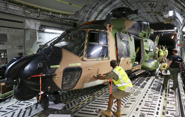 Australian Air Force and Army personnel load a Multi Role Helicopter (MRH 90) onto an Australian Air Force C-17 aircraft before departing from RAAF Base Townsville en route to assist in Cyclone Winston-ravaged Fiji, in Australia in this handout image supplied by the Australian Defence Force on February 23, 2016. (Photo by Reuters/Australian Defence Force)