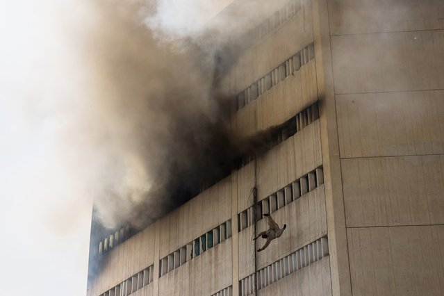 A man overcome by fumes falls out of a window as a fire burns at the Lahore Development Authority (LDA) Plaza on May 09, 2013 in Lahore, Pakistan. (Photo by Daniel Berehulak/Getty Images)
