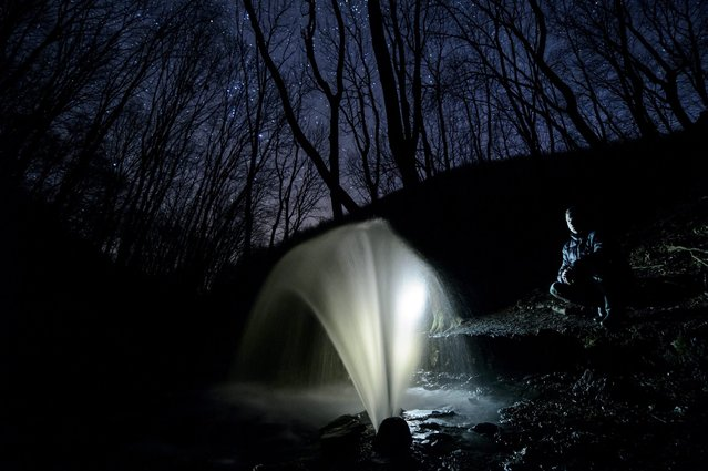 A man watches a periodic karst spring illuminated by a lamp as it wells up in the Bukk Mountains, near Felsotarkany, Hungary, 24 February 2016. Resulted by the rainy weather and the thaw of snow several periodic karst springs have gushed forth in Bukk Mountains. (Photo by Peter Komka/EPA)