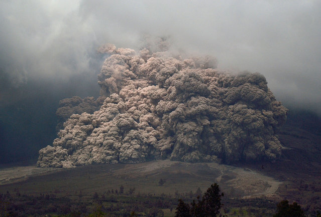 Sinabung mount spews ash to the air during an eruption near from Karo, North Sumatra on January 7, 2014. An Indonesian volcano that has erupted relentlessly for months shot volcanic ash into the air 30 times on January 4, forcing further evacuations with more than 20,000 people now displaced, an official said. (Photo by Sutanta Aditya/AFP Photo)
