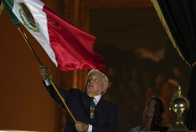 Mexican President Andres Manuel Lopez Obrador waves the national flag after giving the annual independence shout from the balcony of the National Palace to kick off subdued Independence Day celebrations amid the ongoing coronavirus pandemic, at the Zocalo in Mexico City, Wednesday, September 15, 2021. (Photo by Fernando Llano/AP Photo)