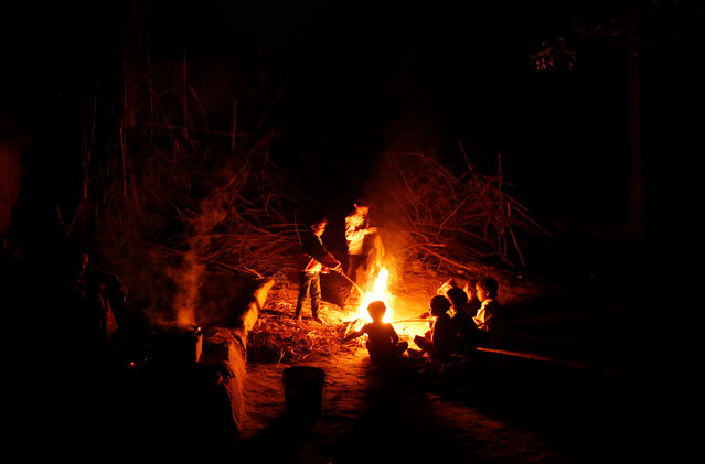 Children of snake charmers sit next to a fire on a cold winter evening in Jogi Dera (snake charmers settlement), in the village of Baghpur, in the central state of Uttar Pradesh, India January 16, 2017. (Photo by Adnan Abidi/Reuters)