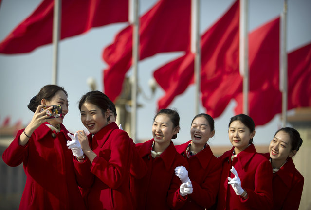 Bus ushers react as they pose for a selfie during a meeting one day ahead of the opening session of China's National People's Congress (NPC) at the Great Hall of the People in Beijing, Monday, March 4, 2019. A year since removing any legal barrier to remaining China's leader for life, Xi Jinping appears firmly in charge, despite a slowing economy, an ongoing trade war with the U.S. and rumbles of discontent over his concentration of power. (Photo by Mark Schiefelbein/AP Photo)