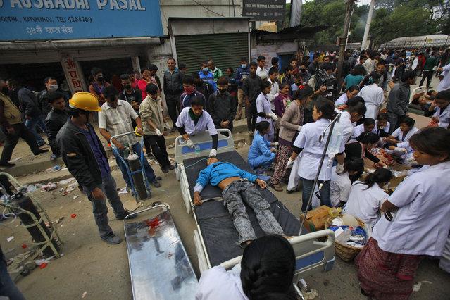 Injured people receive treatment on a street in Kathmandu, Nepal, Saturday, April 25, 2015. (Photo by Niranjan Shrestha/AP Photo)