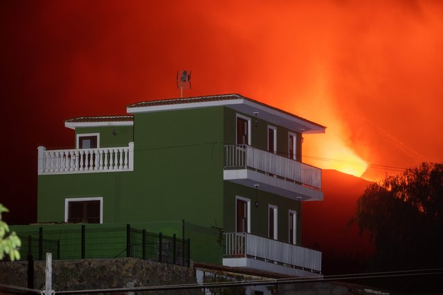 A view of a building as the Cumbre Vieja volcano erupts in the background, in El Paso, La Palma, Canary Islands, Spain, early 06 October 2021. The main cone of the La Palma volcano suffered a partial collapse of its structure 03 October, while effusive activity has increased after 15 days of its beginning. According to experts the volcano is far from ending its volcanic activity. (Photo by Carlos De Saa/EPA/EFE)
