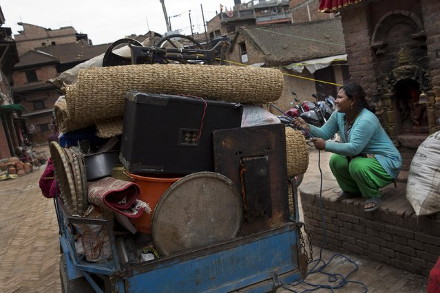 A woman ties up belongings retrieved from the ruins of her home after Saturday's earthquake in Bhaktapur, Nepal, Tuesday, April 28, 2015. (Photo by Bernat Armangue/AP Photo)