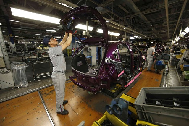 An employee works on the automobile assembly line of a a Citroen C3 car at the PSA Peugeot Citroen plant in Poissy, near Paris, France, April 29, 2015. (Photo by Benoit Tessier/Reuters)