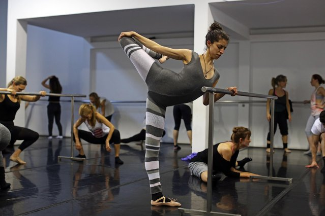 Women stretch during a classic dance class at a dance academy in Lisbon, Wednesday, April 29, 2015. April 29 is marked as the International Dance Day since 1982 and shows were held in different Portuguese cities to promote the art of dancing. (Photo by Francisco Seco/AP Photo)