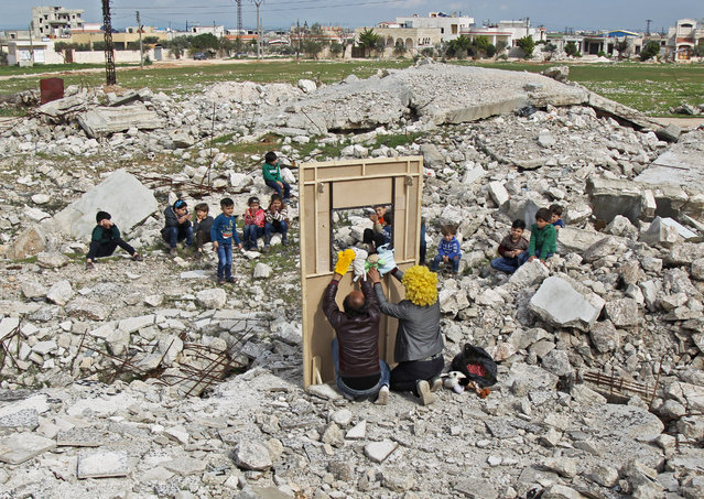 Syrian actor Walid Abu Rashed (yellow wig) and a fellow actor entertain children through a makeshift puppet theatre set up among the rubble of collapsed buildings in the town of Saraqib in the rebel-held northern Idlib province, on March 27, 2019. (Photo by Amer Alhamwe/AFP Photo)