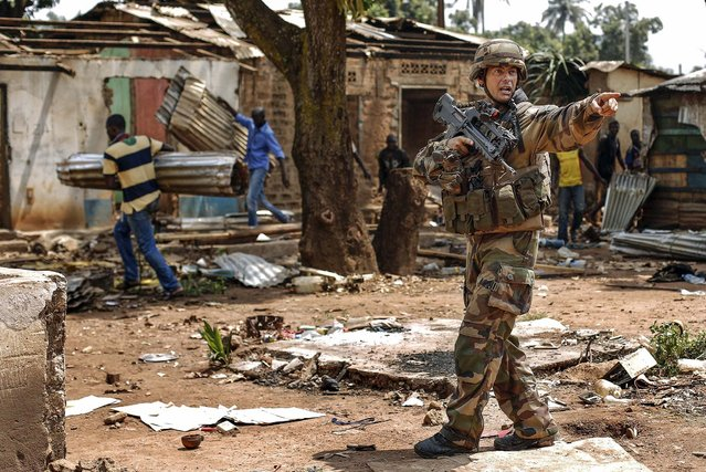 French forces push looters out, in the Miskin district in Bangui, Central African Republic, on February 3, 2014. Fighting between Muslim Seleka militias and Christian anti-Balaka factions continues as French and African Union forces struggle to contain the bloodshed. (Photo by Jerome Delay/Associated Press)