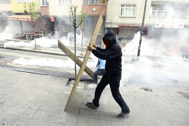 A protester takes cover as police fires tear gas canisters during clashes in Okmeydani neighborhood in Istanbul, Turkey, May 1, 2015. (Photo by Huseyin Aldemir/Reuters)