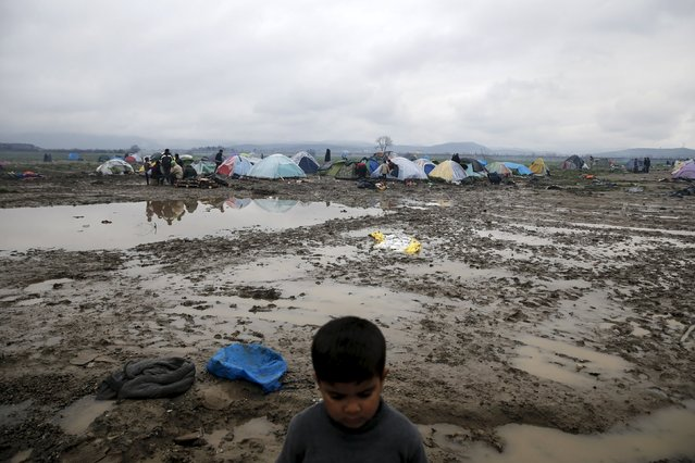 A boy stands on mud as tents are seen in the background at a makeshift camp for refugees and migrants at the Greek-Macedonian border, near the village of Idomeni, Greece March 15, 2016. (Photo by Alkis Konstantinidis/Reuters)