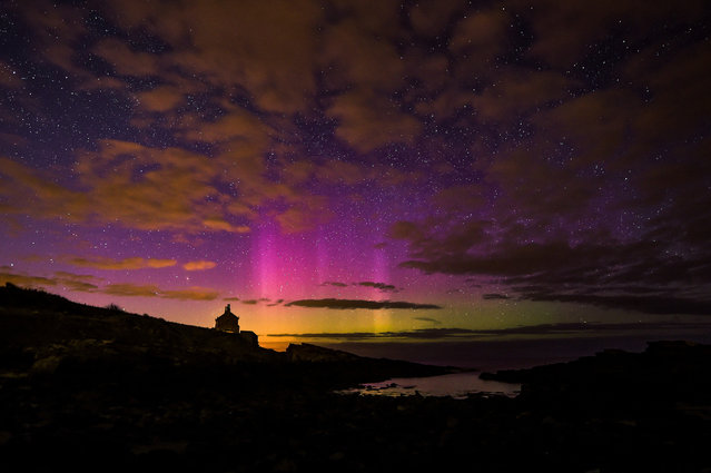 The aurora borealis, or the northern lights as they are commonly known, takes place over the Bathing House in Howick, Northumberland, on April 16, 2015. (Photo by Owen Humphreys/PA Wire)