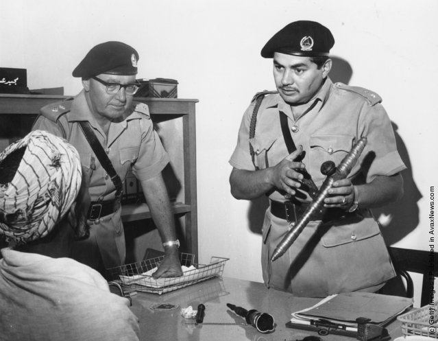 1967:  Two members of the Dubai police force questioning a man about an opium pipe