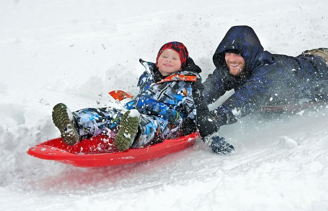 Kayden Vanbenschoten, 4, and his father Justin Edwards, enjoy a wild ride on their sleds at the bottom of a hill near the Turner Ashby High School practice fields, Thursday February 13, 2014 in Bridgewater. Winter Storm snow totals for the Central Shenandoah ranged from 10 to 14 inches with some isolated areas along the Blue Ridge Mountains reporting up to 17 inches. (Photo by Michael Reilly/AP Photo/Daily New-Record)