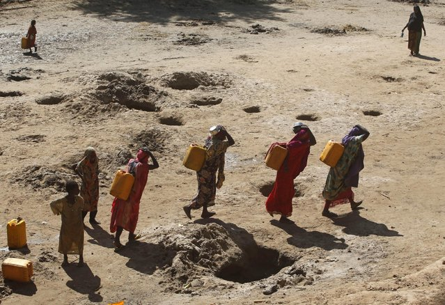 Women carry jerry cans of water from shallow wells dug from the sand along the Shabelle River bed, which is dry due to drought in Somalia's Shabelle region, March 19, 2016. (Photo by Feisal Omar/Reuters)
