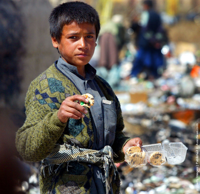 An Afghan boy eats cookies he found at the garbage dump after finding them in the discarded garbage from the Bagram airbase in Afghanistan