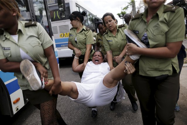 """A member of the """"Ladies in White"""" dissident group shouts as she is carried away by police officers after they broke up a regular march of the group, detaining about 50 people, hours before U.S. President Barack Obama arrives for a historic visit, in Havana, Cuba March 20, 2016. (Photo by Ueslei Marcelino/Reuters)"""