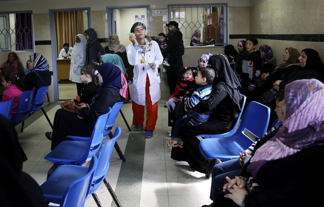 In this Thursday, March 17, 2016 photo, Palestinian clown doctor, 24-year-old Majed Kaloub, entertains children at the Al-Rantisi children's hospital in Gaza City. Kaloub visits three medical centers in the Gaza Strip a week and spends two days at Al-Rantisi, a specialized hospital for children with chronic illnesses. (Photo by Adel Hana/AP Photo)