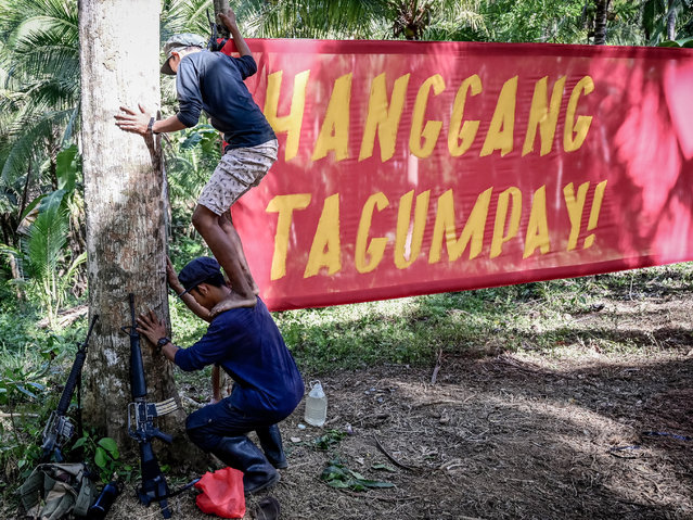 Fighters of the New People's Army-Melito Glor Command (NPA-MGC) hang a banner during their 50th founding anniversary celebration at an undisclosed location in the mountains of Sierra Madre, Philippines, 31 March 2019. (Photo by Alecs Ongcal/EPA/EFE)