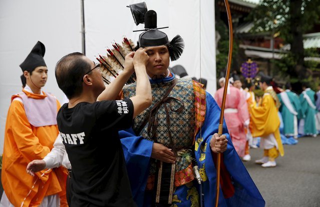 A Shinto studies specialty student in traditional costume is helped by a staff to prepare before a ritual for the Kanda festival at the Kanda-Myojin shrine in Tokyo May 9, 2015. (Photo by Toru Hanai/Reuters)