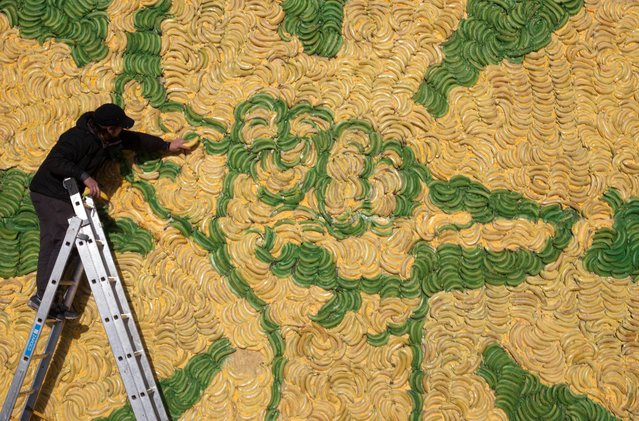 """Artist Toby Crowther adds finishing touches to a giant billboard made from over 5,000 bananas stands on Clapham Common in south London, to mark the start of the Fairtrade Fortnight's """"Stick with Foncho to Make Bananas Fair"""" campaign, on February 24, 2014. (Photo by David Parry/PA)"""