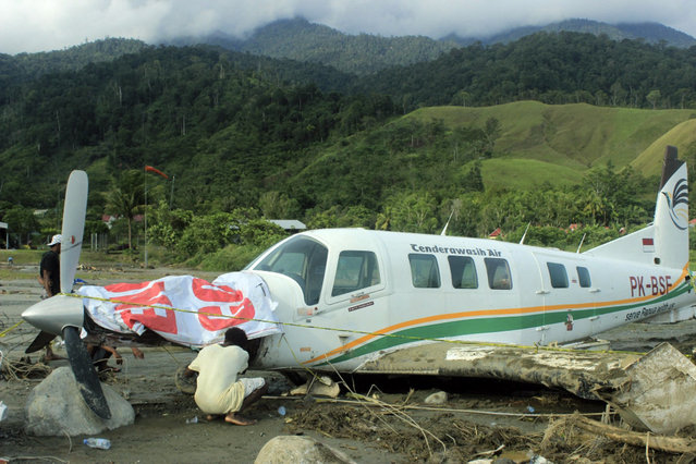 A man look at an airplane washed away by flash flood in Sentani, Papua Province, Indonesia, Sunday, March 17, 2019. Flash flood and mudslides triggered by days of torrential downpour tore through mountain villages in Indonesia's eastern province, killing dozens of people, disaster officials said Sunday. (Photo by Tumbur Gultom/AP Photo)