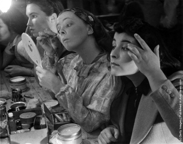 1938: Students at the Royal Academy of Dramatic Art in Bloomsbury, London, applying make-up backstage